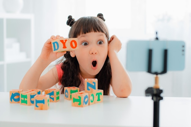 Blogueira fofa brincando com cubos coloridos de madeira com letras e mostrando-os online
