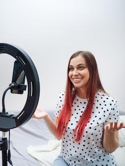 Blogueira fofa e sorridente, com uma camisa branca com bolinhas, falando durante uma transmissão ao vivo, usando um smartphone, uma lâmpada de anel.