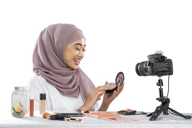 Blogueira hijab animada segurando pó para maquiagem e fazendo vídeos