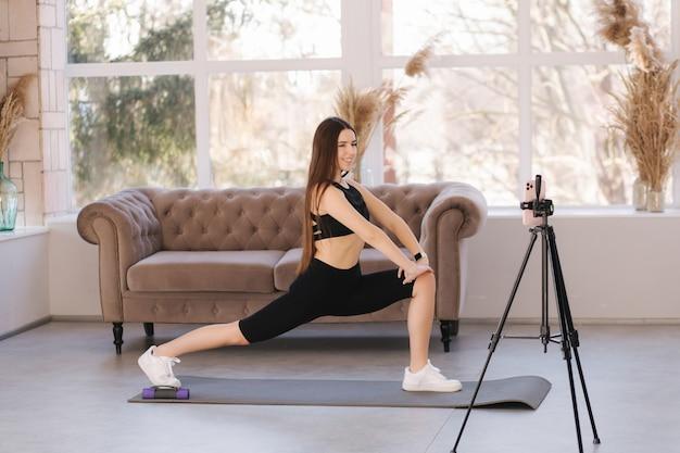 Blogueira jovem atlética em roupas esportivas balck grava um vídeo no telefone enquanto faz exercícios em casa, na sala de estar.