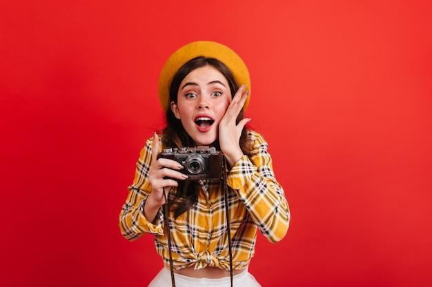 Blogueira linda jovem faz foto na câmera retro. retrato de mulher de olhos verdes em roupa laranja e chapéu na parede vermelha.