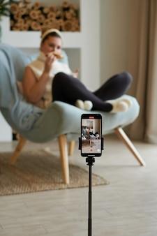 Blogueira morena tira fotos de si mesma em casa no smartphone foco seletivo