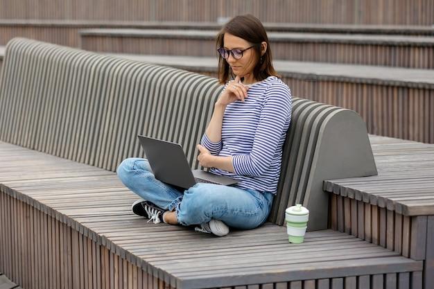 Blogueira ou profissional de marketing jovem e confiante tomando café e trabalhando em seu laptop, trabalhando em um