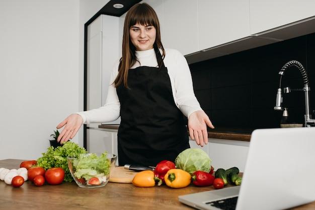 Blogueira sorridente fazendo streaming de culinária com laptop em casa