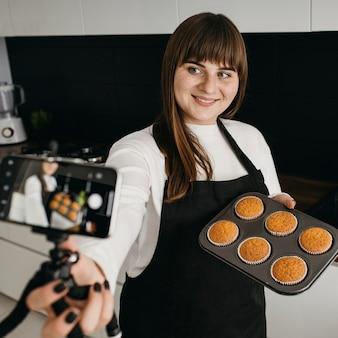 Blogueira sorridente gravando a si mesma com smartphone enquanto prepara muffins