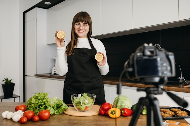 Blogueira sorridente gravando a si mesma enquanto prepara uma salada