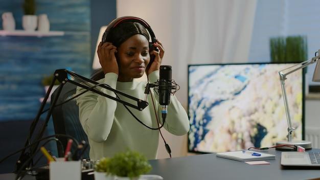 Blogueiro africano sorrindo para o público durante a filmagem do podcast, olhando para a câmera colocando o fone de ouvido. produção no ar, host de transmissão pela internet, streaming de conteúdo ao vivo, gravação de mídia social digital