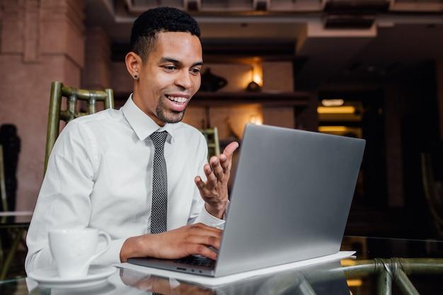 Blogueiro afro-americano expressa positivamente seu laptop, em uma camisa branca, dentro de casa