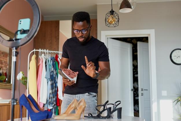 Blogueiro afro de mente aberta fala para a câmera, mostra roupas e sapatos novos