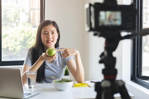 Blogueiro asiático comendo maçã verde e gravando vídeo