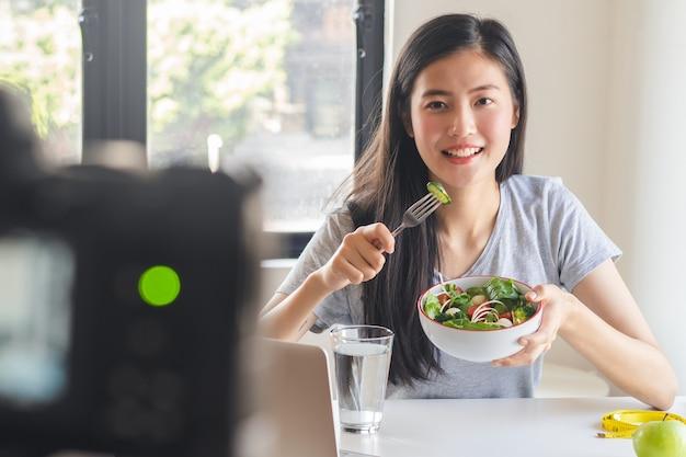Blogueiro asiático comendo salada e gravando vídeo