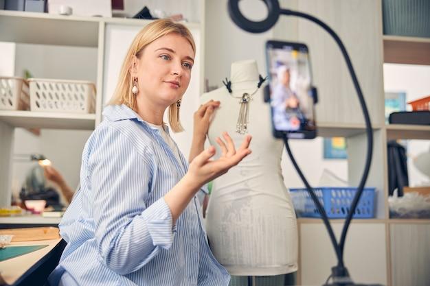 Blogueiro criativo olhando para a câmera do smartphone enquanto apresenta um colar em um suporte fictício
