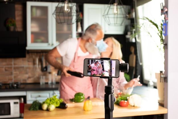 Blogueiro de amante de casal lindo cozinhando ao vivo na cozinha para trabalhar em casa. covid-19. foco seletivo.