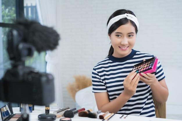 Blogueiro de beleza apresenta cosméticos de beleza enquanto está sentado na câmera frontal para gravação de vídeo