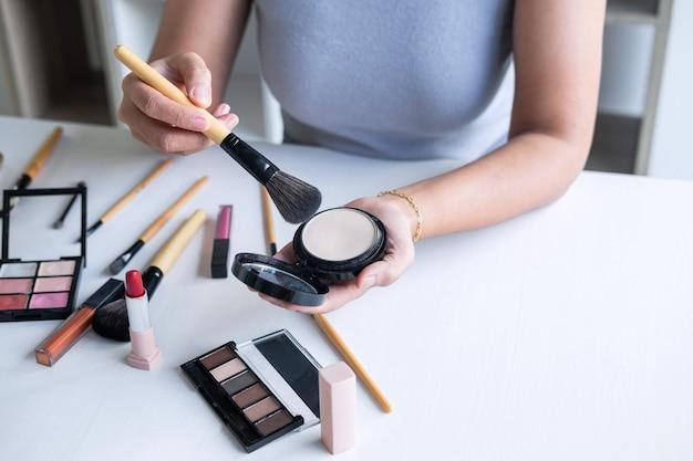Blogueiro de beleza feminino elegante mostrando teste de cosméticos de beleza usando o tutorial de maquiagem do produto cosméticos e produtos de venda