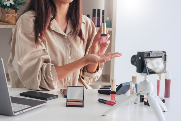 Blogueiro de beleza gravando vídeo e apresentando cosméticos em casa
