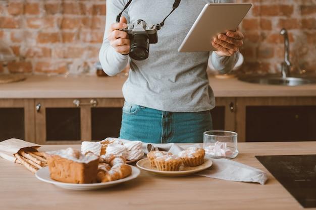 Blogueiro de comida. hobby e estilo de vida. homem com tablet e câmera. variedade de bolos e doces ao redor.