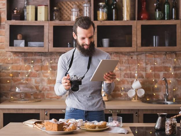 Blogueiro de comida. hobby e estilo de vida. jovem barbudo com tablet e câmera. variedade de bolos e doces ao redor.