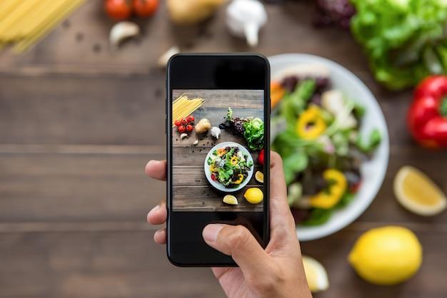 Blogueiro de comida usando smartphone tirando foto de salada bonita