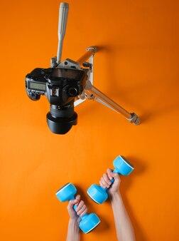 Blogueiro de fitness. mulher segurando halteres de plástico com as mãos e blogando com a câmera no tripé em fundo laranja. vista do topo