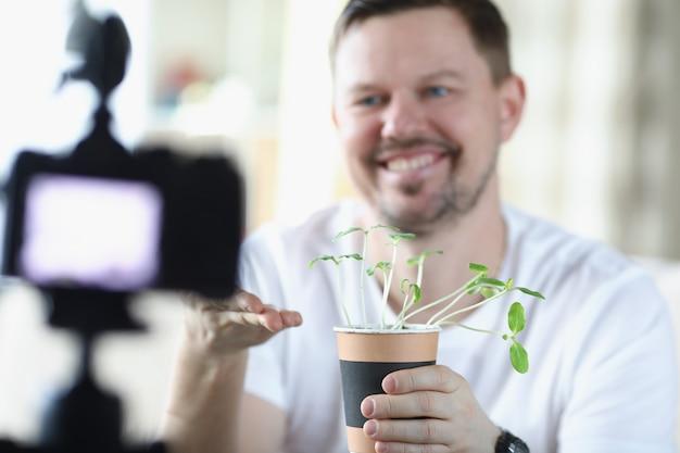 Blogueiro de homem segurando o pote de brotos de planta nas mãos na frente do close da câmera. jardinagem hobby - conceito de ganhar dinheiro online