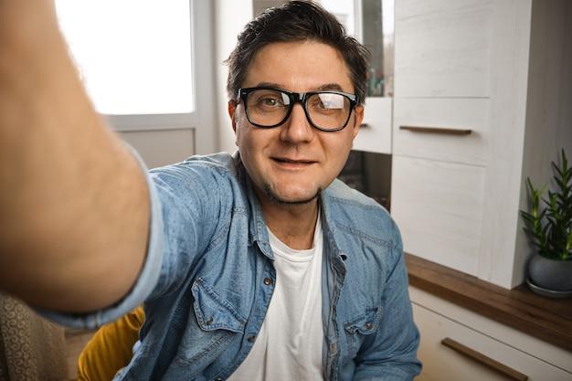 Blogueiro de meia-idade captura-se para vídeo-blog em seu canal diante da câmera em casa
