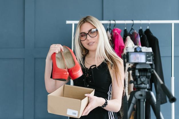 Blogueiro de moda conduzindo uma análise da nova coleção de roupas e acessórios da moda. mulher segurando sapatos de salto alto vermelhos, mostrando-os para a câmera