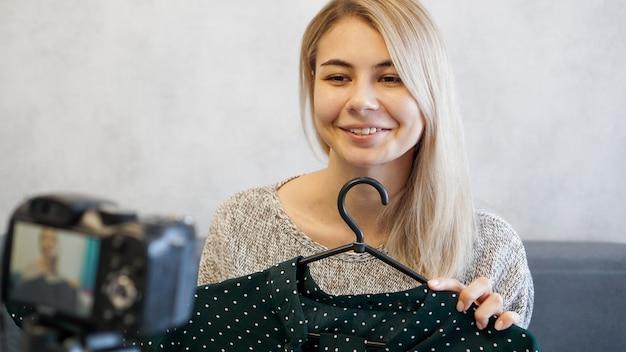 Blogueiro de moda gravando vídeo para blog. mulher na frente da câmera segurando um vestido verde