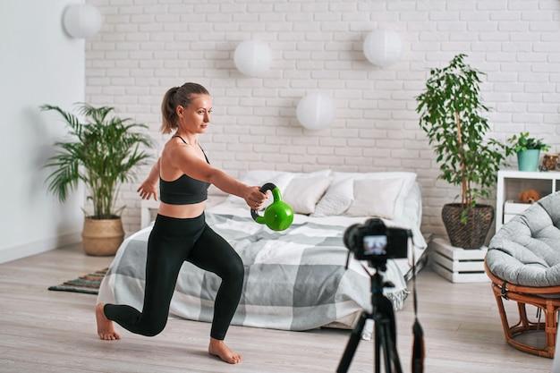 Blogueiro de mulher atlética no sportswear grava vídeo, ela faz exercícios em casa