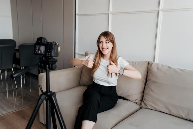 Blogueiro de mulher feliz influenciador mostrando os polegares até a câmera para o seu blog de vídeo na internet