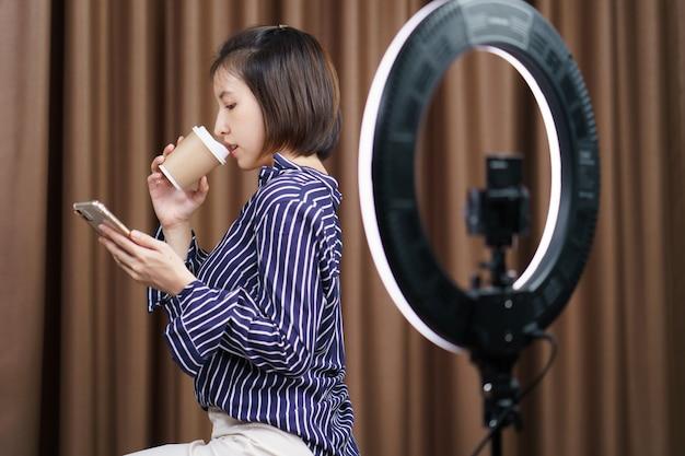Blogueiro de mulher tomando café do copo de papel para viagem durante o uso do telefone móvel com luz do anel.