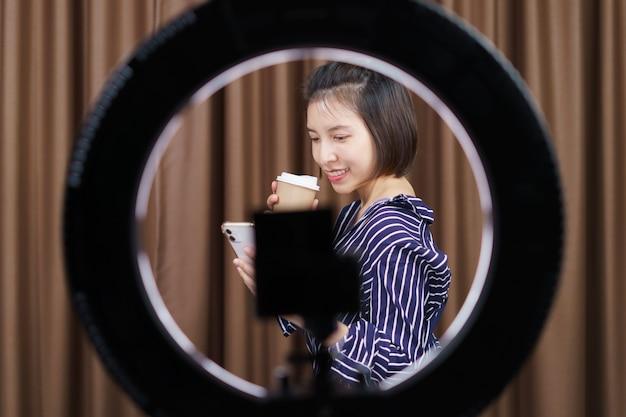 Blogueiro de mulher tomando café do copo de papel para viagem