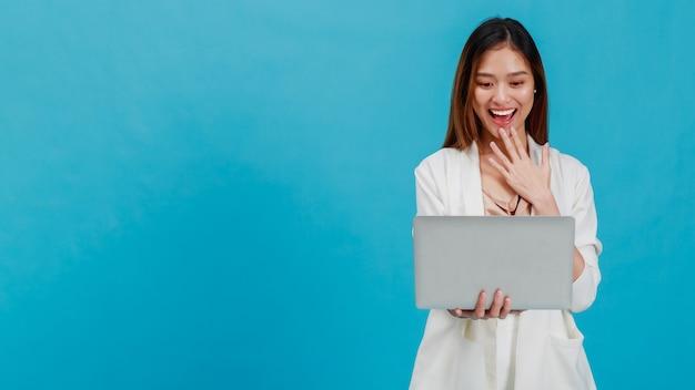 Blogueiro de mulheres de negócios linda asiática usando laptop e isolado em um fundo de cor azul com espaço de cópia de pé. conceito de negócio de compras online com promoção e venda.