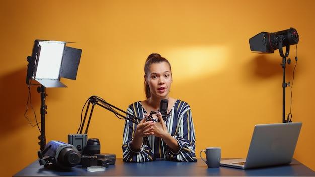Blogueiro de vídeo explicando como usar um filtro de densidade neutra. criador de conteúdo, influenciador estrela de novas mídias em equipamentos de vídeo-foto falante de mídia social para programa de web online na internet