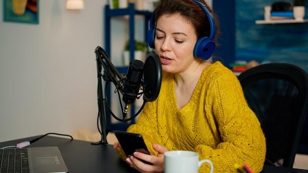 Blogueiro de vídeo lendo perguntas de fãs usando smartphone durante transmissão ao vivo do estúdio de podcast caseiro. mostrar apresentador de transmissão de produção, streaming de conteúdo ao vivo, gravação de mídia digital