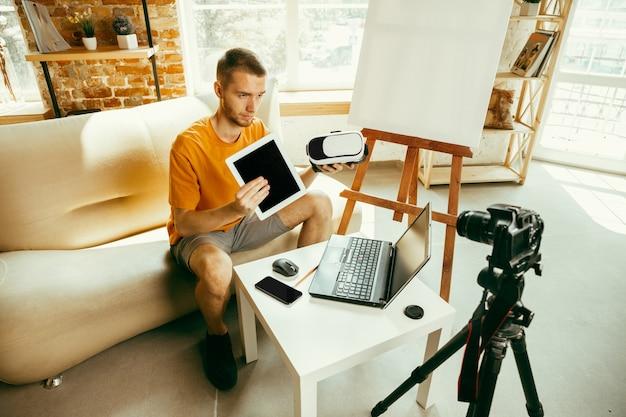 Blogueiro do sexo masculino, caucasiano, com câmera gravando análise de vídeo de gadgets em casa