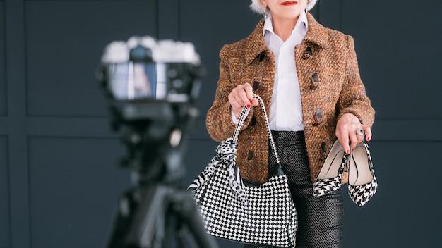 Blogueiro estilista de moda sênior. idosa com roupa de outono na moda, tiro vlog.