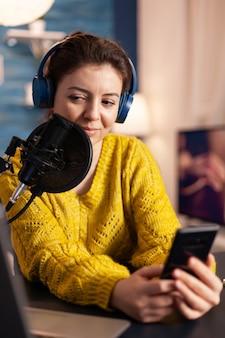 Blogueiro feliz lendo mensagens de fãs usando um smartphone sentado em um estúdio de podcast doméstico durante transmissão ao vivo, gravação
