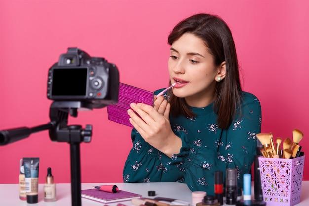 Blogueiro feminino fazendo vídeo para o blog de beleza, sentado à mesa branca contra rosa
