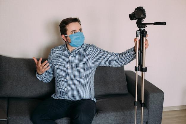 Blogueiro homem influenciador na máscara médica fala sobre coronavírus. o blog de gravação de vídeos do homem diz como se proteger de 2019-ncov.