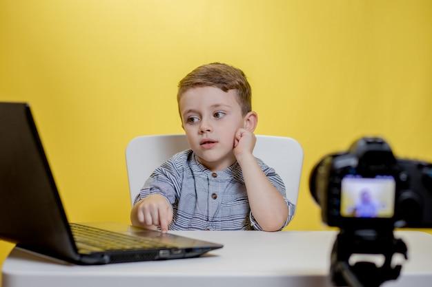 Blogueiro infantil filmando vídeo na câmera trabalhando com o laptop.