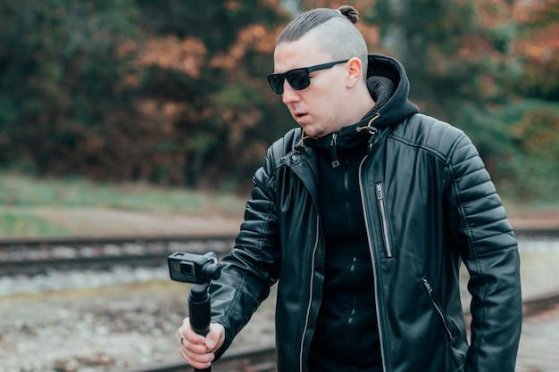 Blogueiro jovem em roupas pretas e óculos de sol fazendo vídeos usando câmera de ação com estabilizador de câmera giratória em floresta de pinheiros