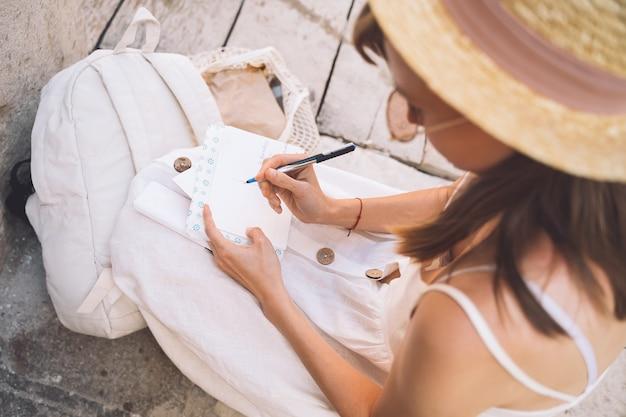 Blogueiro viajante da moda assina cartão postal ou carta para um amigo de veneza