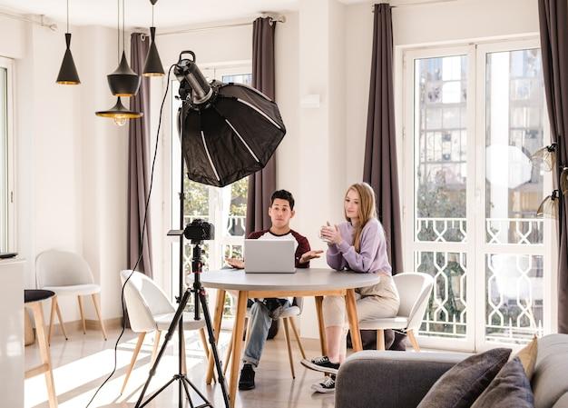 Blogueiros de vídeo fazendo um vídeo com uma câmera profissional em um tripé em casa.