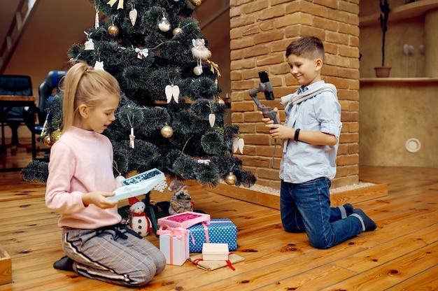 Blogueiros infantis gravam vlog de natal no telefone. kids blogging em home studio, redes sociais para o público jovem, transmissão online pela internet