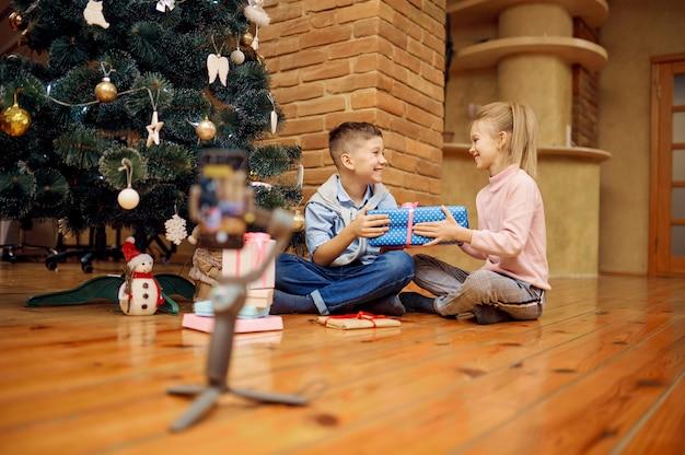 Blogueiros infantis gravam vlog na árvore de natal. kids blogging em home studio, redes sociais para o público jovem, transmissão online