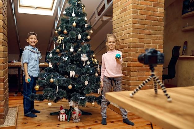 Blogueiros infantis gravando blog de natal na câmera, vloggers