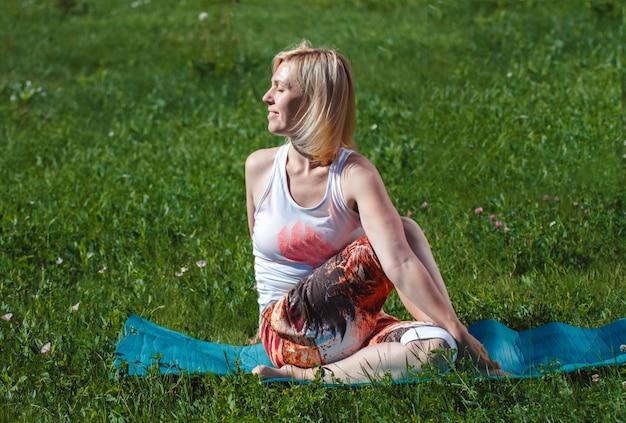 Blonde em um t-shirt branco na grama verde que faz a ioga. tratamento e relaxamento da coluna vertebral. estilo de vida esportivo