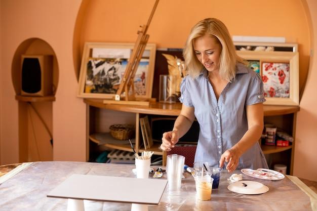 Blonde está trabalhando com tintas em sua oficina de arte, preparando as cores necessárias para sua pintura. . momentos felizes de vida. pinturas de interiores. design e inspiração. trabalhe em casa. estilo de vida.