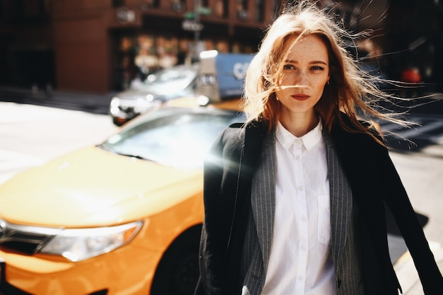 Blonde senhora em casaco preto fica na rua ensolarada em algum lugar da cidade de nova york